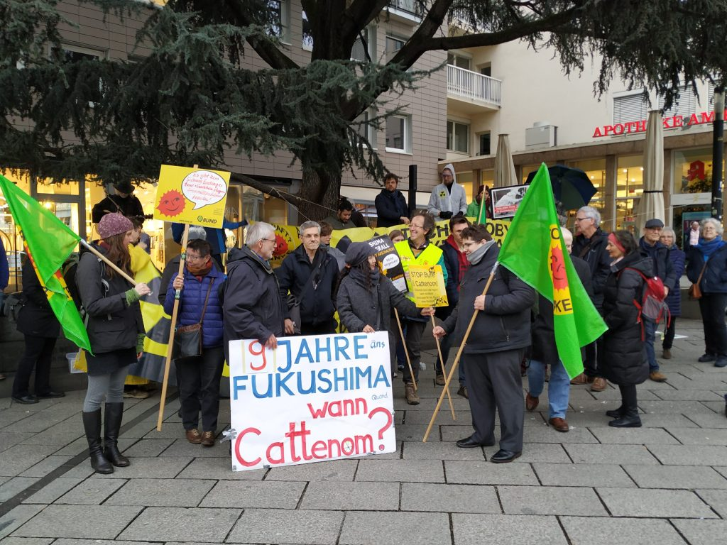 Die Demonstranten gruppieren sich zu einem Foto für die Zeitung und halten Schilder hoch.